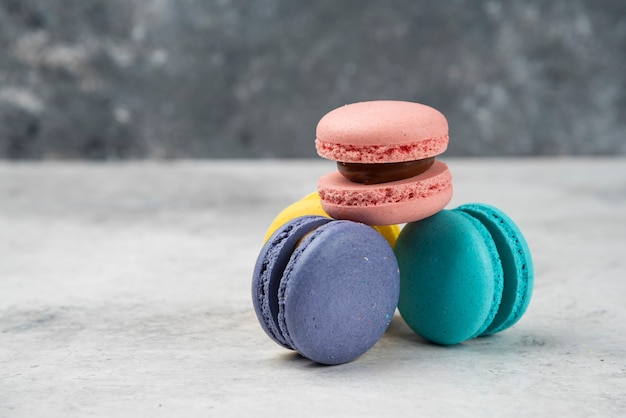 Four multicolored macarons dessert on white table.