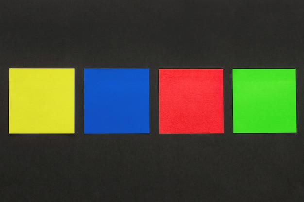 黒の背景、レコードのレイアウトに4つの多色ステッカー。モックアップ。