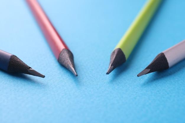파란색 바탕에 4 개의 다 색된 나무 연필 거짓말
