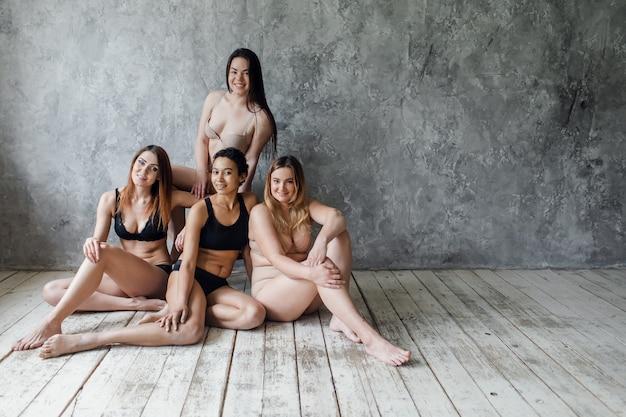 회색, 신체 양성 개념에 포즈를 취하는 속옷에 4 명의 다민족 여성