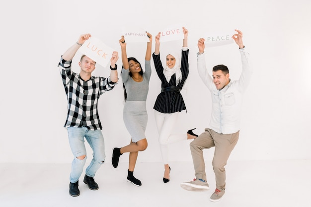 Four multiethnical young smiling people with placards and posters about love, peace and happiness, posing on white background