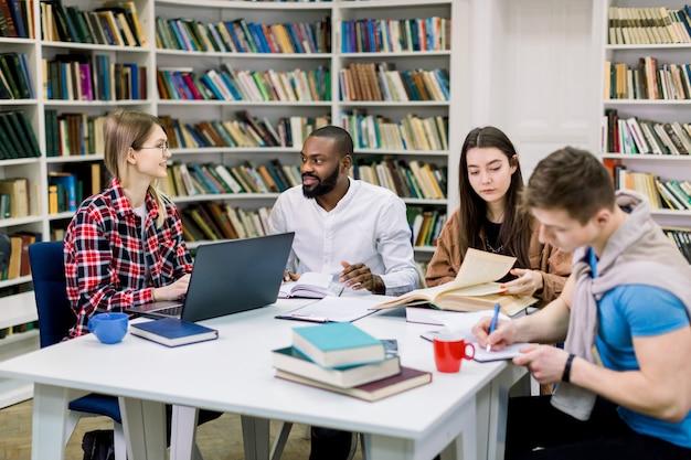 4 многорасовых счастливых студента сидя на таблице в библиотеке пока учащ и работающ на компьтер-книжке.