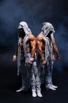 Четыре мускулистых готических человека, стоящих без рубашки на черном фоне, концепция тайны и тайны