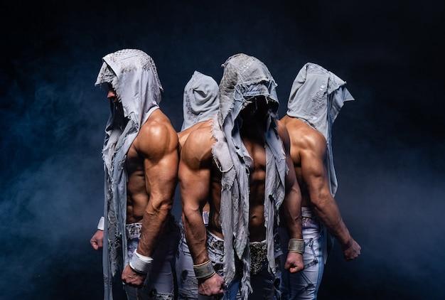 Четыре мускулистых готических человека, стоящих без рубашки на черном фоне