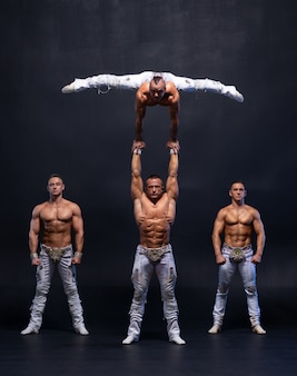 4 명의 근육질 남자가 검은 스튜디오에서 어려운 곡예 트릭을 수행합니다.