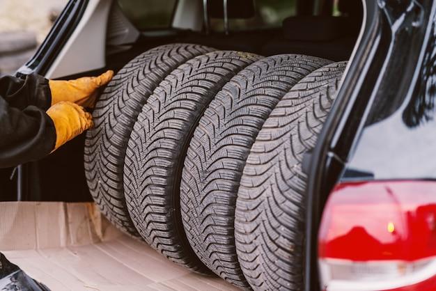 트렁크에 4 개의 새 자동차 타이어. 자동차 서비스. 타이어 설치.