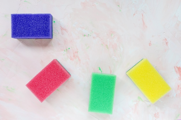 Four new colorful sponges for dishwashing on pink background. domestic household and cleaning