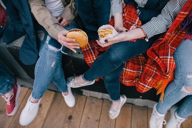 4対の脚の上面図、親しい友人との出会い。お気に入りのジャンクフードで楽しい時間を過ごしている認識できないスタイリッシュな女の子。休息とエンターテインメント、陽気な雰囲気のコンセプトを持つレジャー