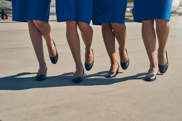 비행장에서 활주로를 걷는 네 쌍의 여성 다리