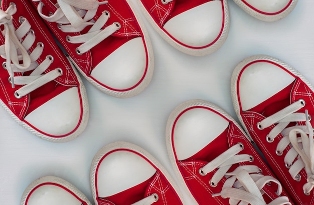 Four pairs of red sneakers on a white wooden surface