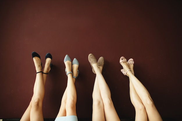Four pairs of women's legs in the shoes