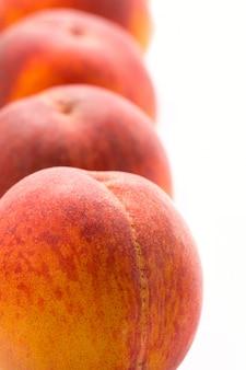 Four peaches closeup on white background