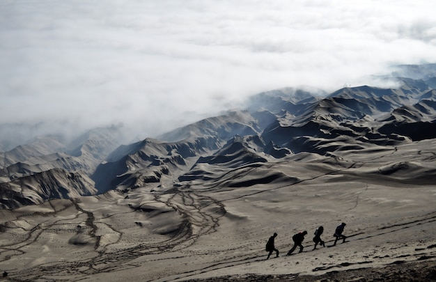 Four people are hiking the sand dunes on the slope of bromo crater, located in indonesia