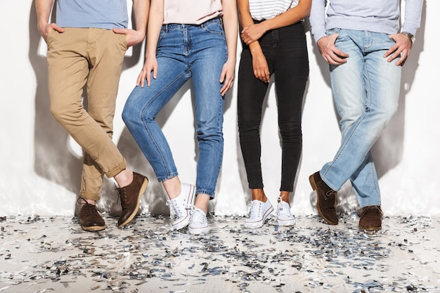 Four people dressed in jeans standing on a floor
