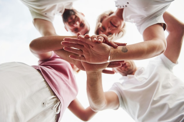 Four people fold hands together as a sign of their team work