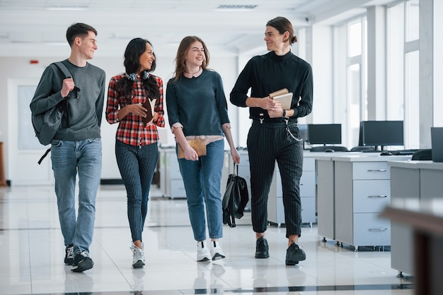 Four people. group of young workers walking in the office at their break time.