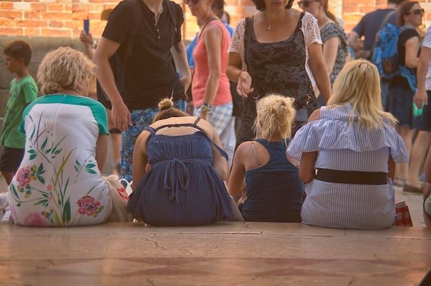 Четыре человека сидят на полу и пожимают плечами
