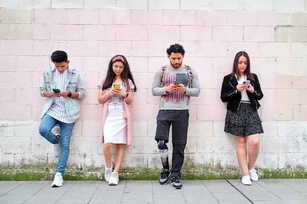 전화기를 사용하여 거리 벽에 기대어 서 있는 4명의 사람들
