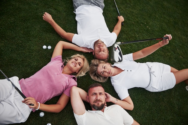 Four people, two guys and two girls, lie on the golf course and relax after the game