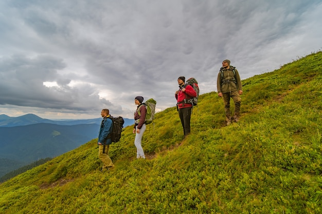 The four people with backpacks standing on the green mountain