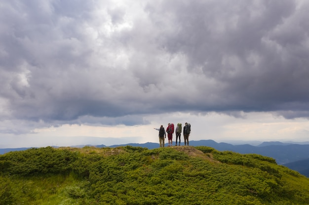 The four people with backpacks standing on the mountain against beautiful clouds