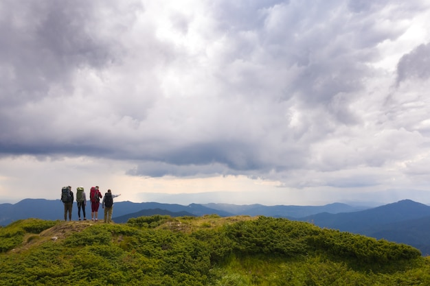 The four people with backpacks standing on a mountain against beautiful clouds