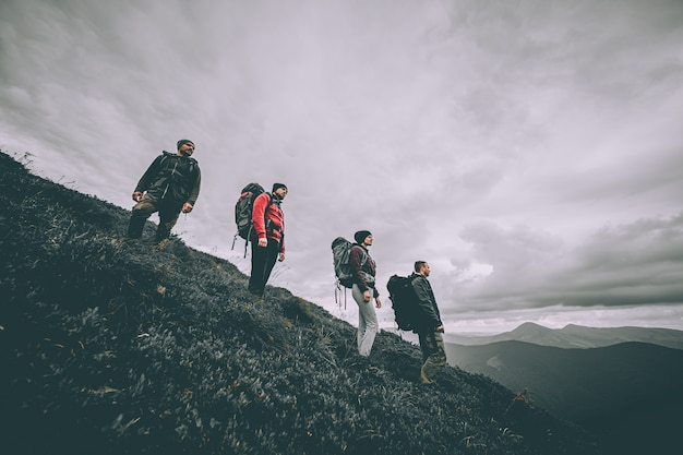 The four people with backpacks standing on the mountain