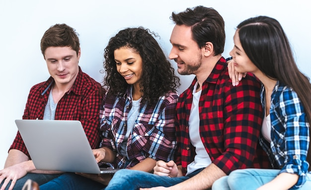 The four people with a laptop sitting on the white wall background