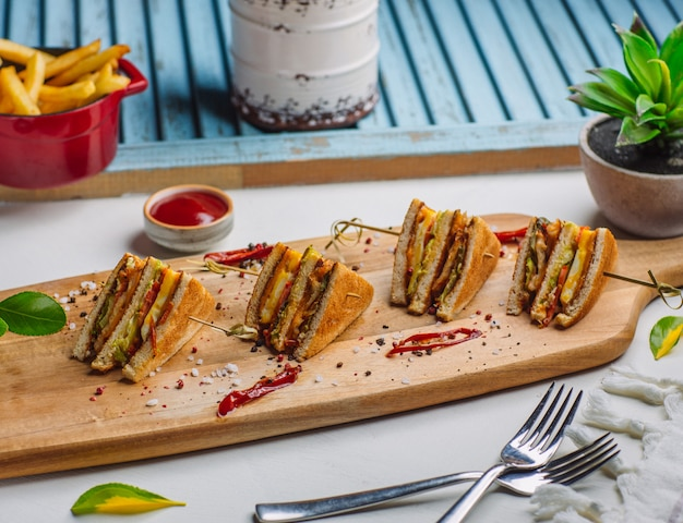 Four pieces of club sandwich on wooden board with french fries, ketchup