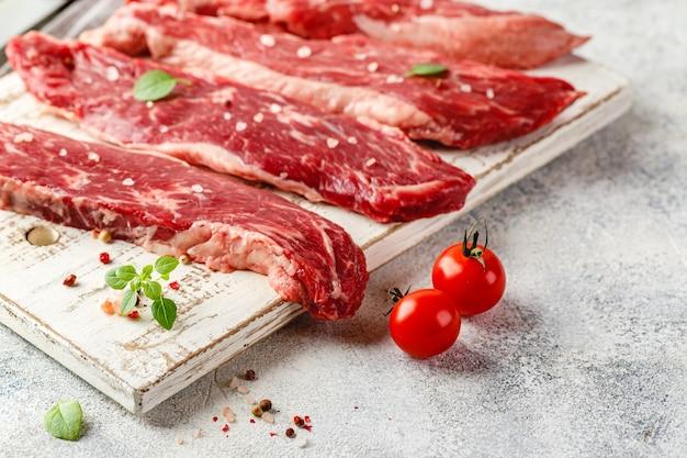 Четыре куска сырого говяжьего стейка на деревянной разделочной доске, нож, соль, перец, помидоры и масло в бутылке