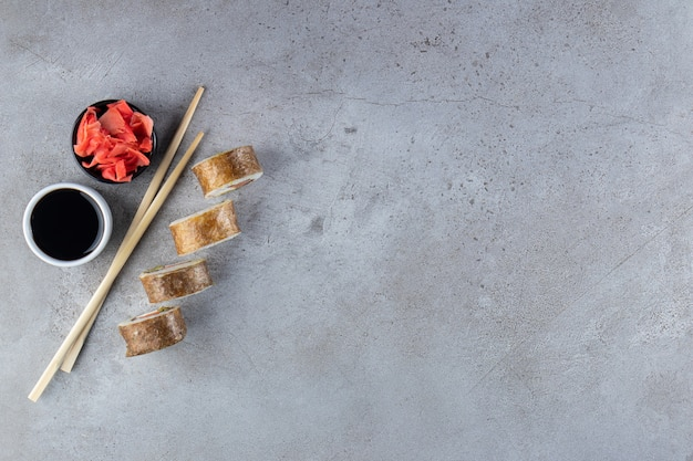 Four pieces of sushi rolls, ginger and soy on stone background.