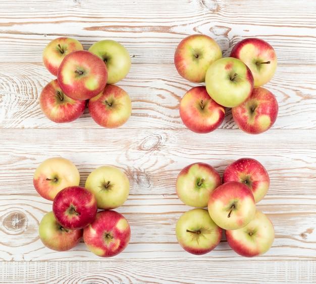 テキスト上面図の場所を持つ赤と緑の柔らかいリンゴの4つの山。木製の素朴な表面に山積みされた有機リンゴ