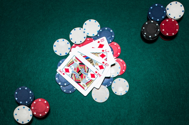 Four playing cards showing a royal flush in diamond over the casino chips on green poker table