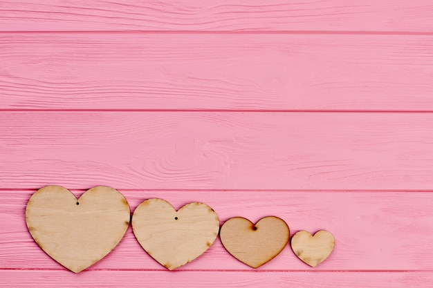 Four plywood hearts on colorful background. row of wooden hearts on pink wooden background with copy space. valentines day greeting card.