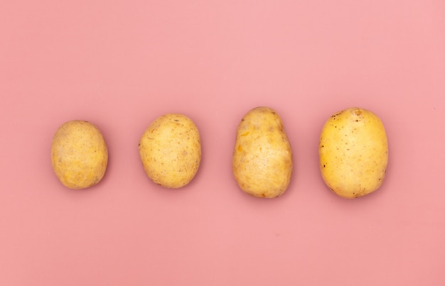 Four potatoes on pink background