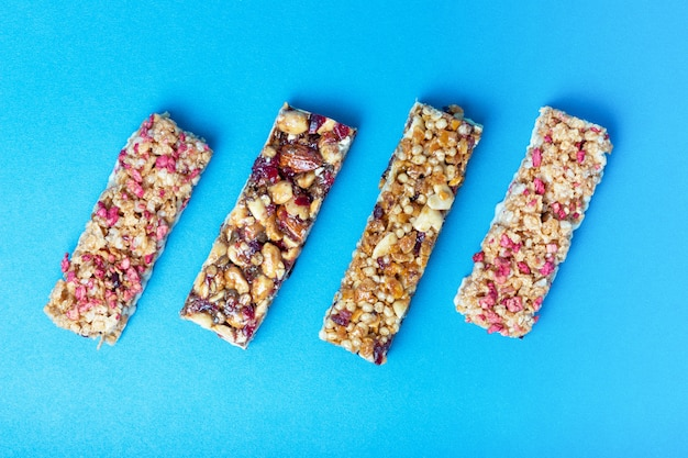Four protein bars with cereals isolated on blue