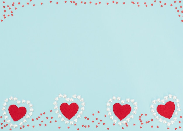 Four red felt hearts inside a hearts made of small pearl hearts on blue background.