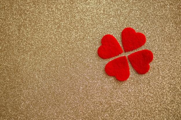 バレンタインデーの金の光沢のある背景に4つの赤いハート