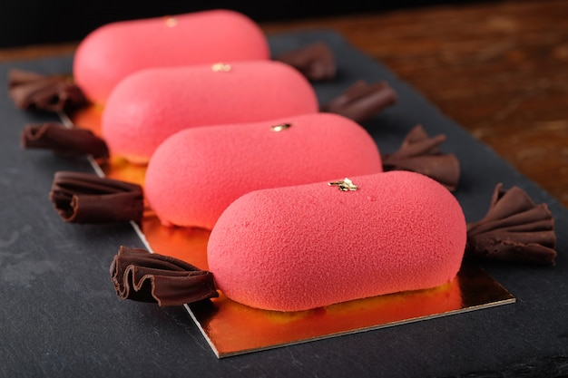 Four red mini mousse cakes with chocolate velour in shape of candy