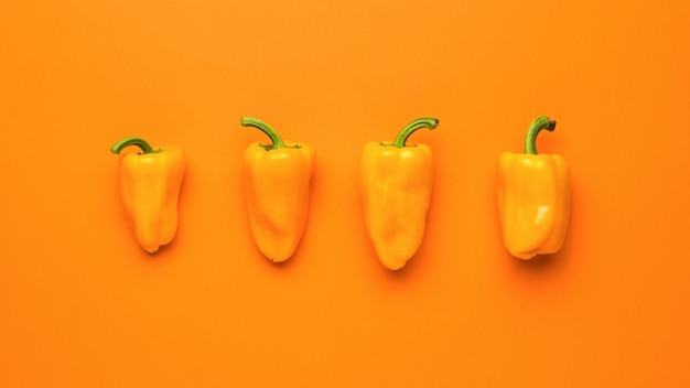 Four ripe orange peppers on an orange background. vegetarian food.