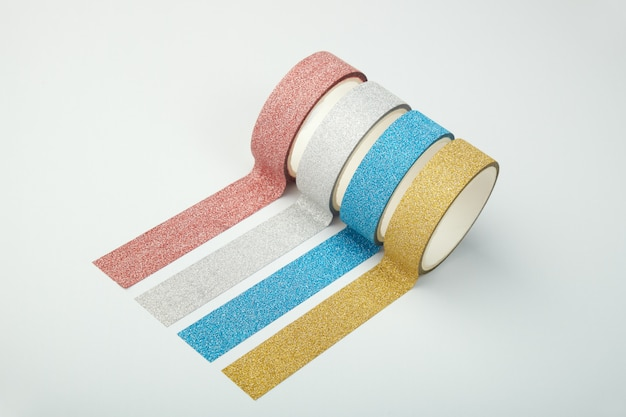 Four rolls of glitter tape and parallel strips on white table