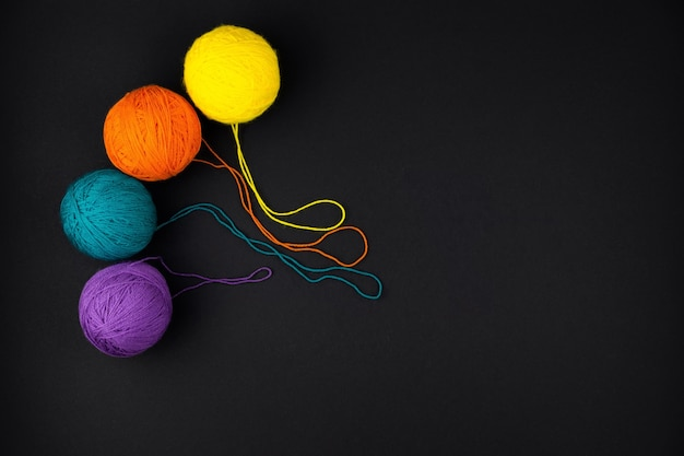 Four round balls of wool yarn on a black background