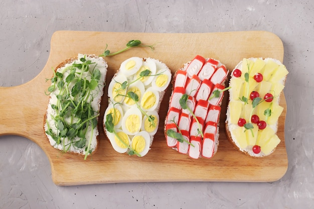 Four sandwiches on toast with peas microgreens, pineapples, red currant, crab sticks and quail eggs on wooden board