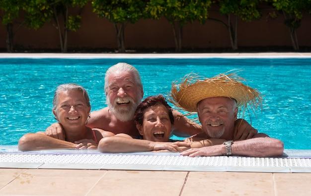 Четыре пожилых человека вместе в прозрачной воде бассейна, наслаждаясь летом. счастье под ярким солнцем. бирюзовая вода