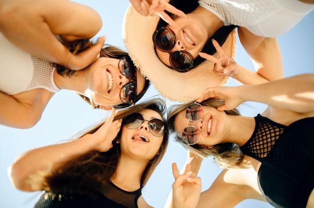Четыре сексуальные женщины в солнцезащитных очках, вид снизу, вечеринка у бассейна на открытом воздухе. красивые девушки отдыхают у бассейна в солнечный день, летние каникулы привлекательных подруг