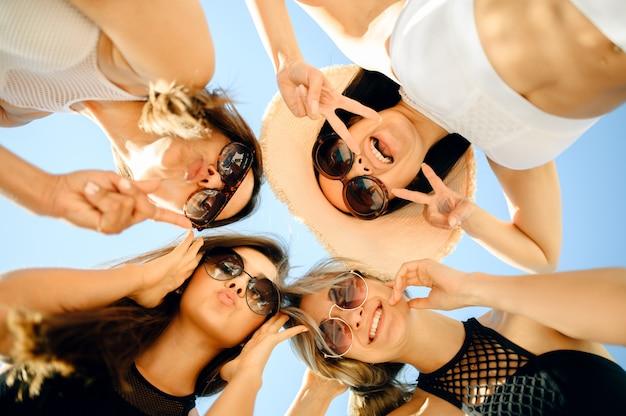 Четыре сексуальные женщины в солнцезащитных очках, вид снизу