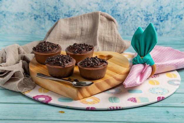 Четыре маленьких бригадных торта с шоколадным вкусом на пасхальном столе с розовой салфеткой, кольцо для салфеток, похожее на кроличьи ушки, тематический сусплат
