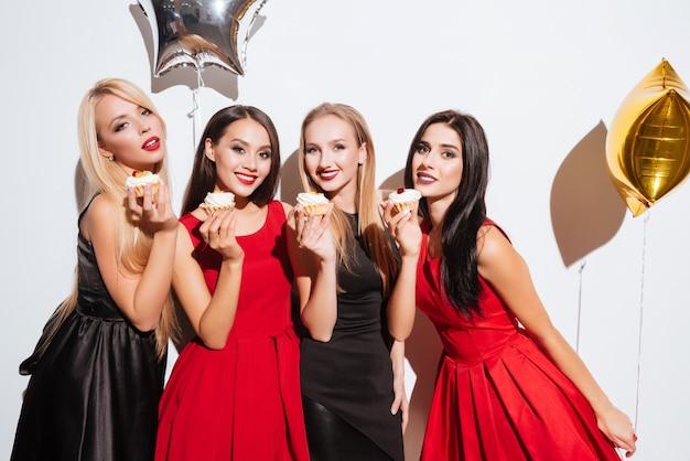 Четыре улыбающихся великолепных молодых женщины едят кексы на вечеринке на белом фоне