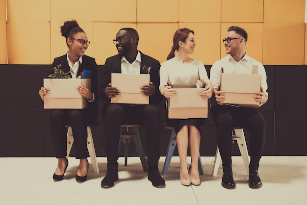 Four smiling people are sitting with office boxes.