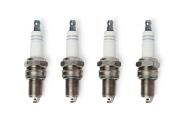Four spark plugs isolated on white background. top view.